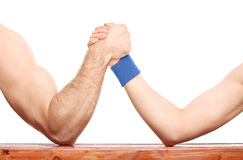Arm wrestling between a muscular arm and skinny one. Close-up on an uneven arm wrestling contest between a muscular arm and a skinny one isolated on white Stock Photo