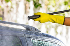 Arm with yellow glove holding high pressure water. Cleaner and using it on car door windows Stock Photo