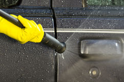 Arm with yellow glove holding high pressure water. Cleaner and using it on car door windows Stock Images