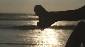 Arm of young woman playing with sand. Female hand pouring sea sand through her fingers at sunset against an ocean stock footage
