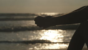 Arm of young woman playing with sand. Female hand pouring sea sand through her fingers at sunset against an ocean stock video