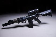 Arma automatica con il silenziatore e la portata ottica fotografia stock