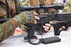 Arma automatica e un uomo in uniforme del cammuffamento Fotografia Stock