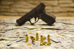 A arma borrada com as balas estabelecidas em dólares borrados fotos de stock royalty free