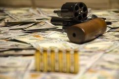 A arma com as balas borradas estabelecidas em dólares borrados foto de stock