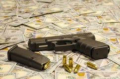 A arma com as balas borradas estabelecidas em dólares borrados imagem de stock