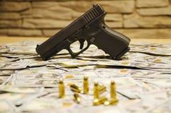 A arma com as balas borradas estabelecidas em dólares borrados fotos de stock royalty free
