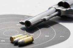 arma com as balas de 9mm no alvo Fotos de Stock