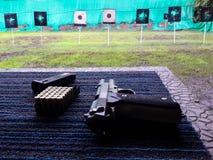 Arma com balas bloco e compartimento na tabela contra o alvo de tiro no clube de esporte de tiro fotografia de stock