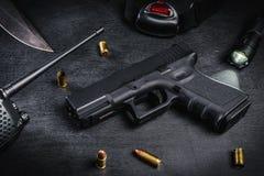 Arma, cuchillo y cartuchos en una tabla negra Imagenes de archivo