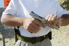 Arma da mão da carga do homem na escala de acendimento Fotos de Stock