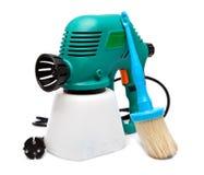 Arma de espray eléctrico para la coloración, para la pulverización del color y una brocha. Aún-vida en un fondo blanco Imagen de archivo