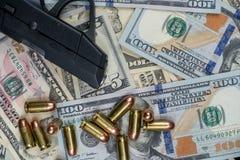 Arma de fogo preta e close-up das balas em uma pilha da moeda do Estados Unidos contra um fundo preto foto de stock