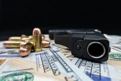 Arma de fogo preta e close-up das balas em uma pilha da moeda do Estados Unidos contra um fundo preto foto de stock royalty free