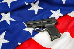 Arma de la mano en bandera americana Fotos de archivo