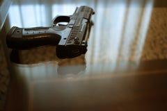 Arma de la pistola en la tabla en sitio fotografía de archivo