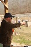 Arma de mano barbuda del tiroteo del hombre joven en las blancos de la gama de la pistola Imagen de archivo libre de regalías