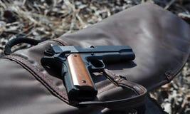 Arma de mano de 45 calibres colocada encima de una caja de arma de cuero imágenes de archivo libres de regalías