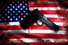 Arma de mano con la mancha de sangre en bandera americana control de armas de la reforma fotografía de archivo libre de regalías