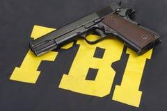 Arma de mano del potro m1911 en el uniforme del fbi imágenes de archivo libres de regalías