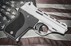 Arma de mano encima de la bandera americana fotos de archivo