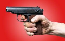 Arma de mano lista para encender Pistola a disposición sobre rojo Foto de archivo