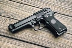 Arma de mano, primer de la pistola de 9m m en fondo de madera Imágenes de archivo libres de regalías