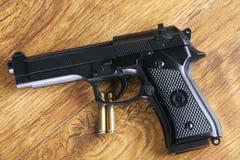 Arma de mano y dos balas de cobre amarillo en fondo de madera Imagen de archivo
