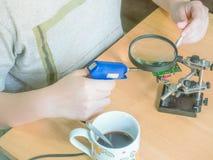 A arma de solda azul à disposição da moça asiática cria o projec de DIY Foto de Stock