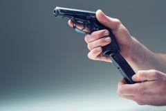 Arma del arma La mano de los hombres que sostiene un arma pistola de 9 milímetros Foto de archivo libre de regalías