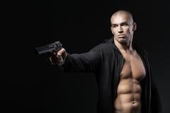 Arma del tiroteo del hombre aislado en negro Fotografía de archivo libre de regalías