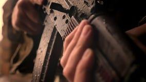 Arma della tenuta del soldato del og delle mani del primo piano e fucilazione della pistola molto attentamente, esterno piovoso d archivi video