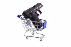 Arma em um carrinho de compras Fotos de Stock Royalty Free