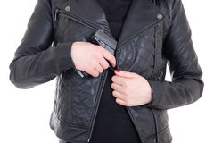 Arma escondendo da mulher no casaco de cabedal isolado no branco Fotos de Stock Royalty Free