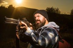 Arma farpada da terra arrendada do homem do caçador e passeio no rifle Hunter Silhouetted da floresta no por do sol bonito Caça d fotos de stock