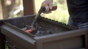 A arma impetuosa inflama carvões Fumo dos carvões A arma impetuosa inflama carvões em um mangeada O homem inflama carvões na vídeos de arquivo