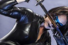 Arma, menina com espada do katana. vestido no látex preto, st cômico Fotos de Stock