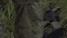 Arma militar que miente en la hierba cerca de las piernas del soldado almacen de metraje de vídeo