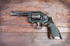 Arma negro del revólver con las balas aisladas en fondo de madera Imagenes de archivo