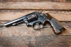Arma negro del revólver con las balas aisladas en fondo de madera Imágenes de archivo libres de regalías