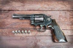Arma negro del revólver con las balas aisladas en fondo de madera Fotografía de archivo
