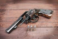 Arma negro del revólver con las balas aisladas en fondo de madera Foto de archivo libre de regalías