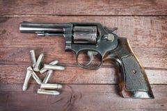Arma negro del revólver con las balas aisladas en fondo de madera Fotografía de archivo libre de regalías