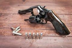 Arma negro del revólver con las balas aisladas en fondo de madera Foto de archivo