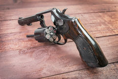 Arma negro del revólver con las balas en fondo de madera Fotografía de archivo