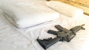 a arma pôs sobre um branco confortável do colchão e do descanso Imagens de Stock