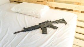 a arma pôs sobre um branco confortável do colchão e do descanso Fotografia de Stock Royalty Free