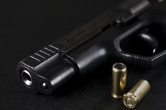 A arma preta encontra-se em um fundo preto ao lado das balas fotos de stock royalty free