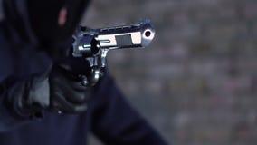 Arma que apunta criminal en la víctima y dinero y joyas exigentes, robo de la calle almacen de video