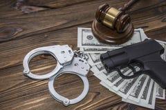 Arma traumático, dinero, martillo del juez foto de archivo